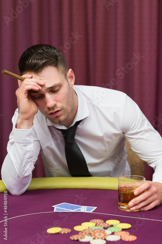 Man leaning on poker table holding cigar