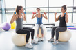 Three women lifting weights on exercise balls