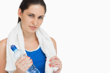 Brunette in sportswear with a towel and a bottle