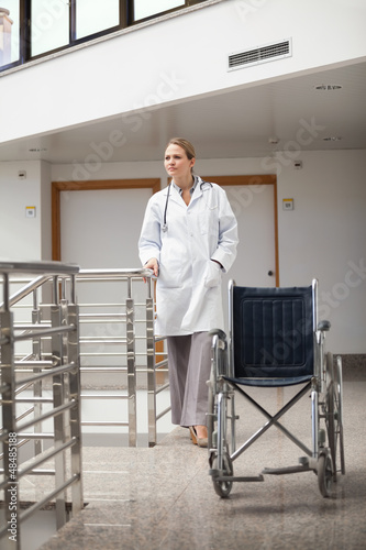 Thoughtful doctor standing next to a wheelchair