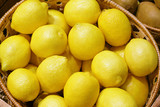 Closeup of many yellow juicy lemon fruits in basket