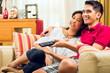 Asian couple watching tv