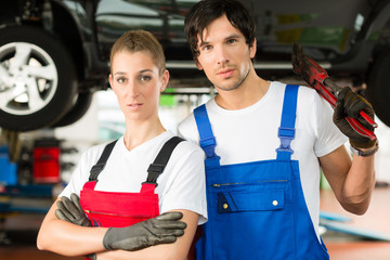 Car mechanics male and female in front of auto