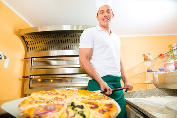 Man pushing the finished pizza from the oven