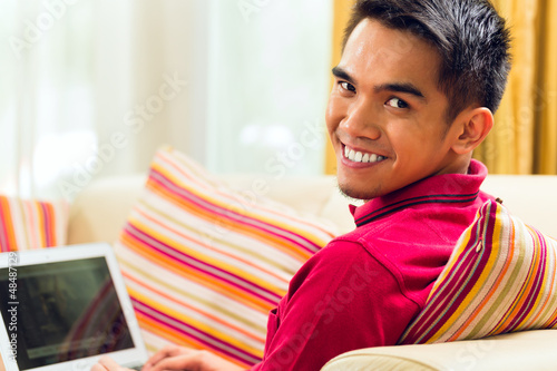 Asian man sitting on couch surfing the internet