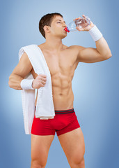 a muscular male drinking water from bottle