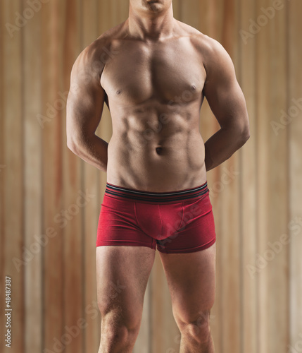 a muscular male torso on a background of the wooden wall