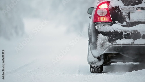 Car on winter road with smoke from exhaust pipe