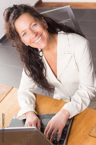 Dark haired Woman in front of Notebook