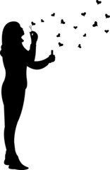 Young girl blowing soap bubbles in heart shaped silhouette