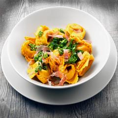 piatto di ravioli con speck e verdura