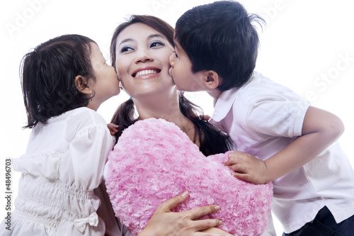 Happy mother kissed by children - isolated