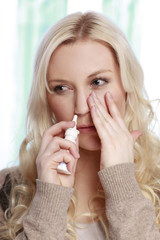 Hübsche Frau nimmt Meerwasser Nasenspray