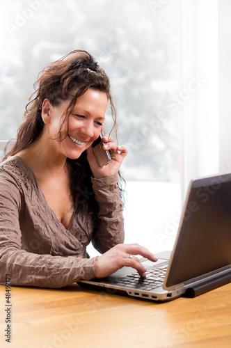 Lachende Frau telefonierend vor Notebook