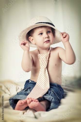 Portrait of the little boy with tie and hat