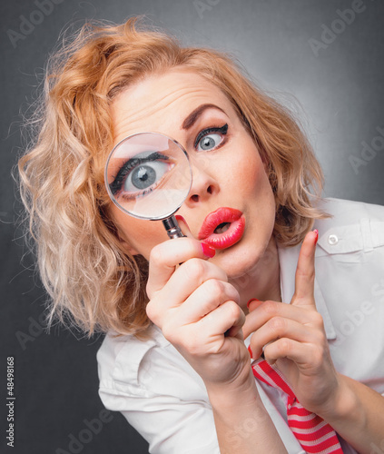 Woman with magnifier, close-up expressive face of a funny woman