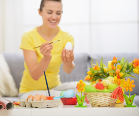 Closeup on table with Easter decoration and woman drawing on egg