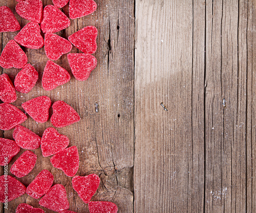 Sticker heart shape candy on wooden plank
