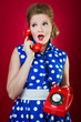 50s style housewife gossiping in a red vintage phone