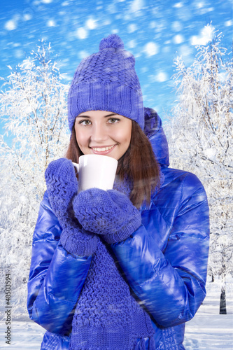 Winter girl drinking warm beverage.