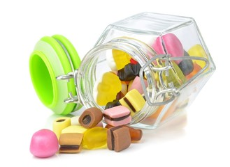 A glass jar of mixed sweets lying on a white background