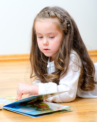 Pretty little girl lying on the floor and reading a book