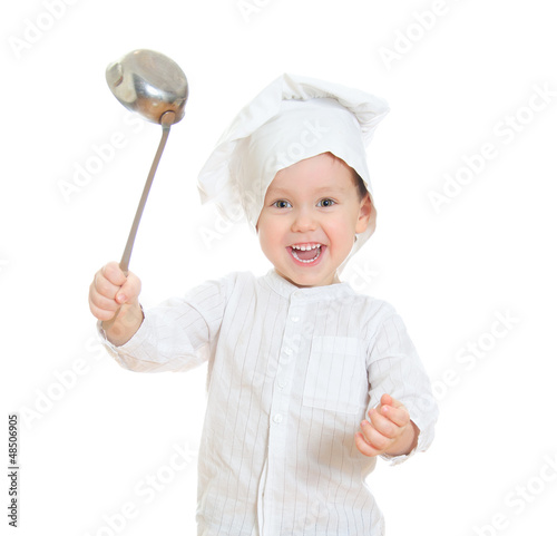 Smiling little boy in chef's hat holding ladle.