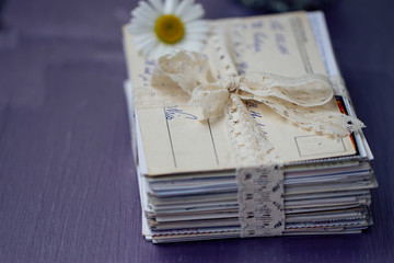 stack of old letters with chamomile