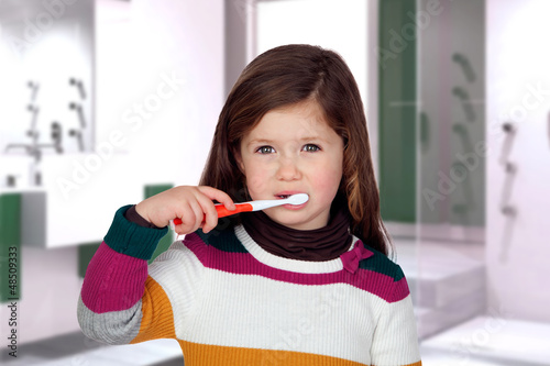 Pretty little girl brushing teeth