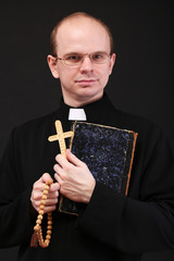 Young pastor with wooden cross and Bible, isolated on black