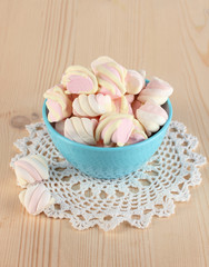 Gentle marshmallow in bowl on wooden table close-up