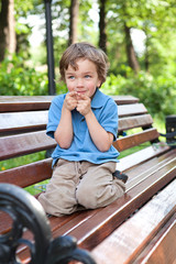 little boy sits on bench in park