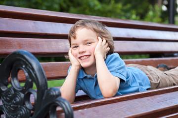 Little boy lying on park bench