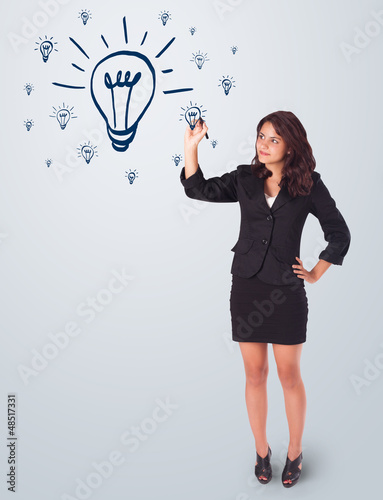 Woman drawing light bulb on whiteboard