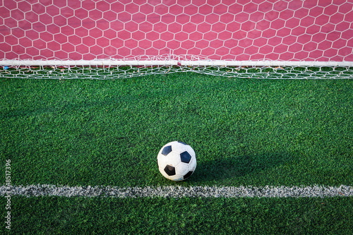 soccer ball on green grass in goal net