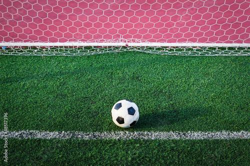 soccer ball on green grass in goal net