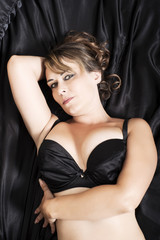attractive woman in lingerie lying on black satin sheets