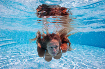 Close up portrait of underwater woman in swimming pool.
