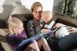 Mutter ließt Kindern auf dem Sofa eine Geschichte vor
