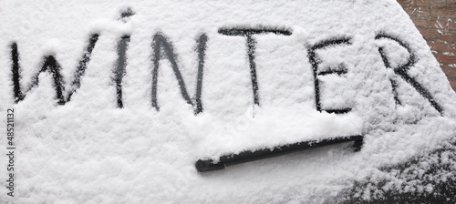 Word Winter written on snowy rear screen car