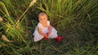 Cute baby in a white dress sitting in tall grass