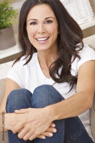 Happy Smiling Beautiful Woman Sitting on Sofa