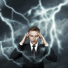 Young businessman thinking on lightnings background