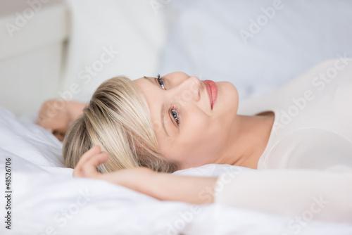 attraktive frau liegt entspannt auf dem bett