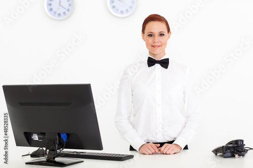 pretty young receptionist standing by hotel reception
