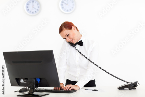 hotel receptionist talking on phone while checking on computer