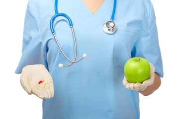Doctor showing pill and green apple