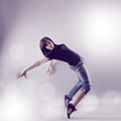 Teenage girl dancing hip-hop leaning on back in studio