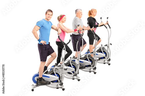 A group of people working on a cross trainer machine