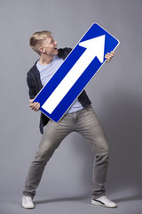 Friendly man holding upward pointing direction arrow sign.